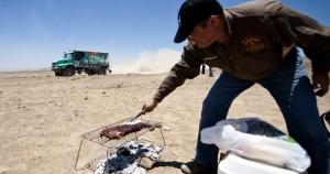 Τουρίστας κανει το barbecue του ενώ στο βάθος ο Ολλανδός οδηγός Gerard De Rooy.Πηγή φώτο:Martin Bernetti/AFP/Getty Images)