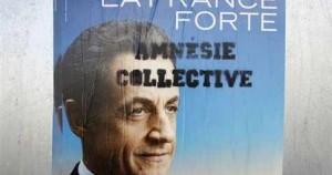 «Η Γαλλία δυνατή» γράφει η αφίσα του Νικολά Σαρκοζί και από κάτω έχει συμπληρωθεί το σύνθημα «συλλογική αμνησία».