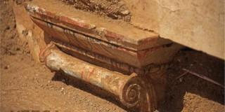 Κάτω από τη βάση των Σφιγγών, το ανώτερο τμήμα του μαρμάρινου θυρώματος, το οποίο καλύπτεται με fresco σε μίμηση ιωνικού επιστυλίου και φέρει διακόσμηση με κόκκινο, μπλε και μαύρο χρώμα