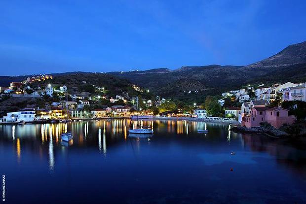 Νυχτερινή πανοραμική άποψη της Ασσου, με τα φώτα του χωριού να καθρεφτίζονται στα ήρεμα νερά του λιμανιού